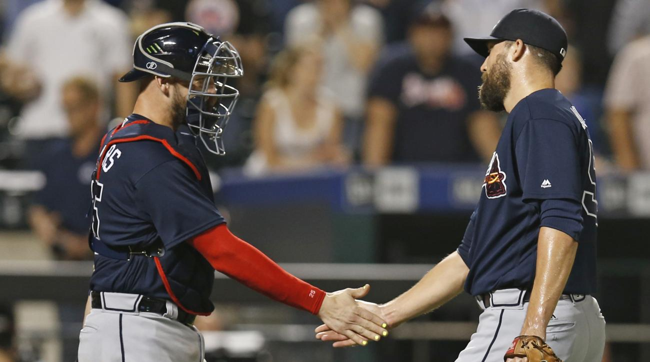 Atlanta Braves' catcher Tyler Flowers, left, congratulates Atlanta Braves relief pitcher Jim Johnson (53) after Johnson struck out Yoenis Cespedes to earn a save in the Braves 5-4 victory over the New York Mets in a baseball game, Tuesday, Sept. 20, 2016,