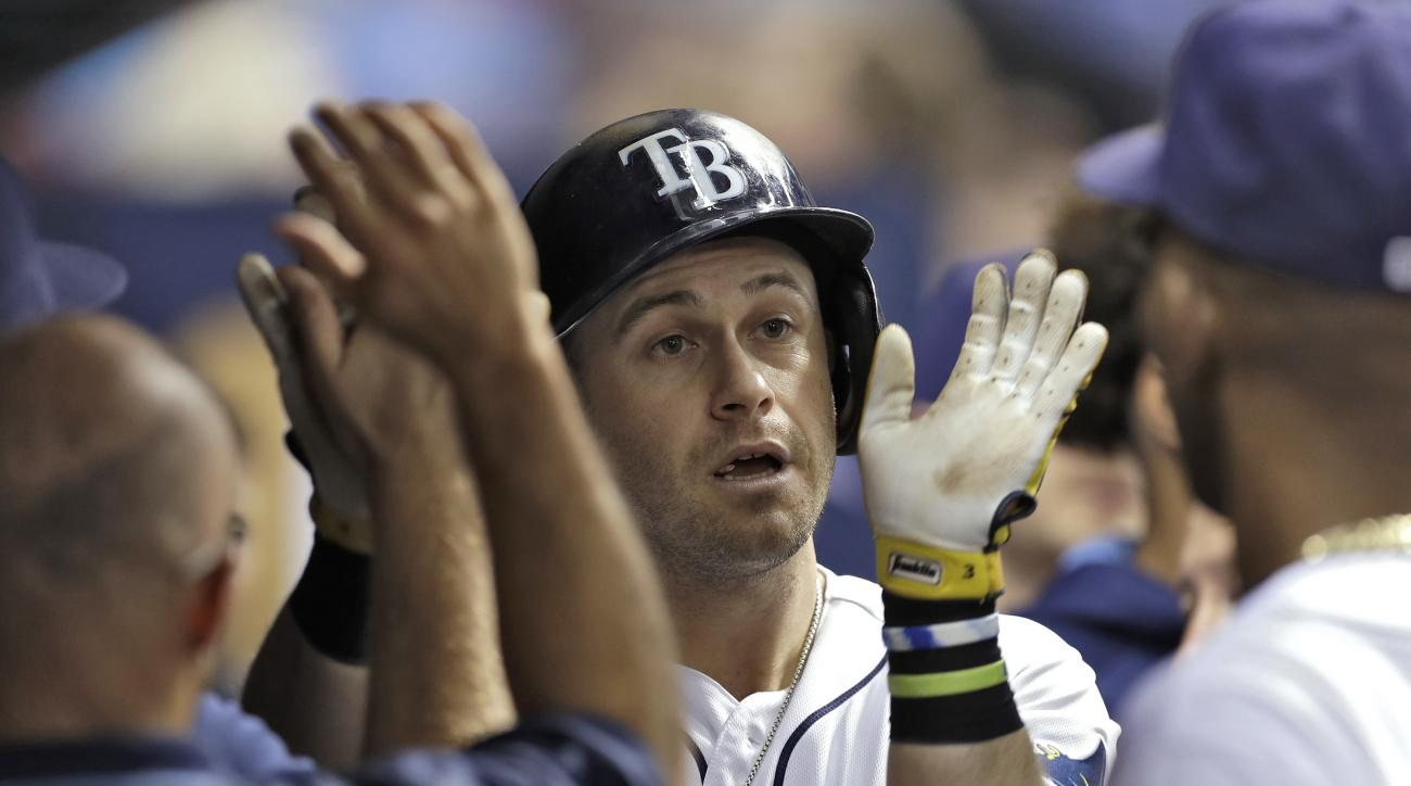 Tampa Bay Rays' Evan Longoria, center, high fives teammates in the dugout after his home run off New York Yankees starting pitcher Masahiro Tanaka during the third inning of a baseball game Wednesday, Sept. 21, 2016, in St. Petersburg, Fla. (AP Photo/Chri