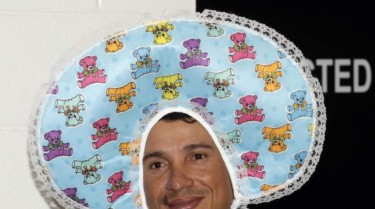 New York Yankees second baseman Ronald Torreyes wears a baby's hat as he leaves the locker room after a baseball game against the Tampa Bay Rays Thursday, Sept. 22, 2016, in St. Petersburg, Fla. Yankees' rookies wore baby clothes as part of hazing before