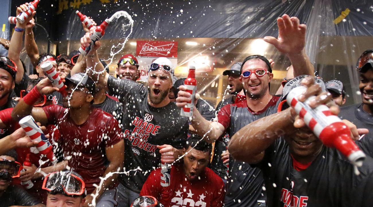 Washington Nationals' Bryce Harper, center left, and Max Scherzer, center right, celebrate with teammates after clinching the National League East following a 6-1 win over the Pittsburgh Pirates in a baseball game in Pittsburgh, Saturday, Sept. 24, 2016.