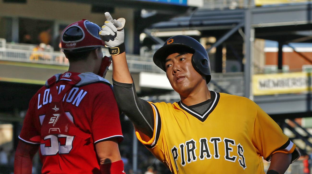 Pittsburgh Pirates' Jung Ho Kang (27) crosses home plate in front of Washington Nationals catcher Jose Lobaton after hitting a two-run home run off Nationals pitcher Koda Glover during the seventh inning of a baseball game in Pittsburgh, Sunday, Sept. 25,