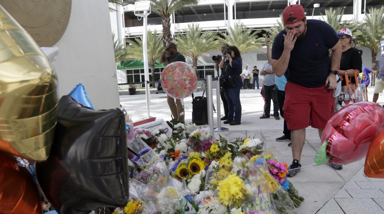 Daniel Isusi, 24, of Miami, wipes tears after leaving flowers at a makeshift memorial outside Marlins Park for Miami Marlins pitcher Jose Fernandez, before a baseball game between the Marlins and the New York Mets, Monday, Sept. 26, 2016, in Miami. Fernan