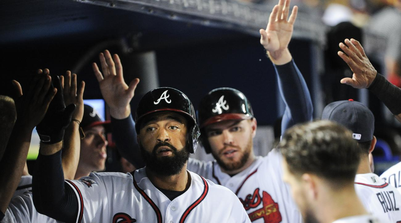 Atlanta Braves' Matt Kemp, left, and Freddie Freeman are congratulated in the dugout after Kemp's two-run home run during the fourth inning of a baseball game against the Philadelphia Phillies, Wednesday, Sept. 28, 2016, in Atlanta. (AP Photo/John Amis)
