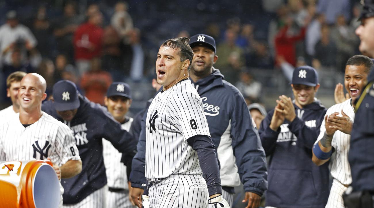New York Yankees' Mark Teixeira , center, reacts after teammates doused him with ice water and Gatorade after hitting a ninth-inning, walk off grand slam in a baseball game against the Boston Red Sox in New York, Wednesday, Sept. 28, 2016. Yankees pitcher