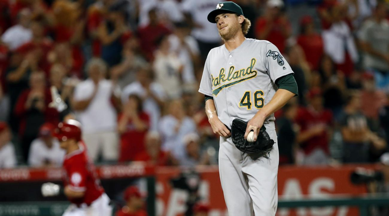 Los Angeles Angels relief pitcher Cory Rasmus looks over at the A's bench, as Los Angeles Angels' Kole Calhoun, left, rounds third base after hitting a two-run home run during the fourth inning of a baseball game in Anaheim, Calif., Wednesday, Sept. 28, 2