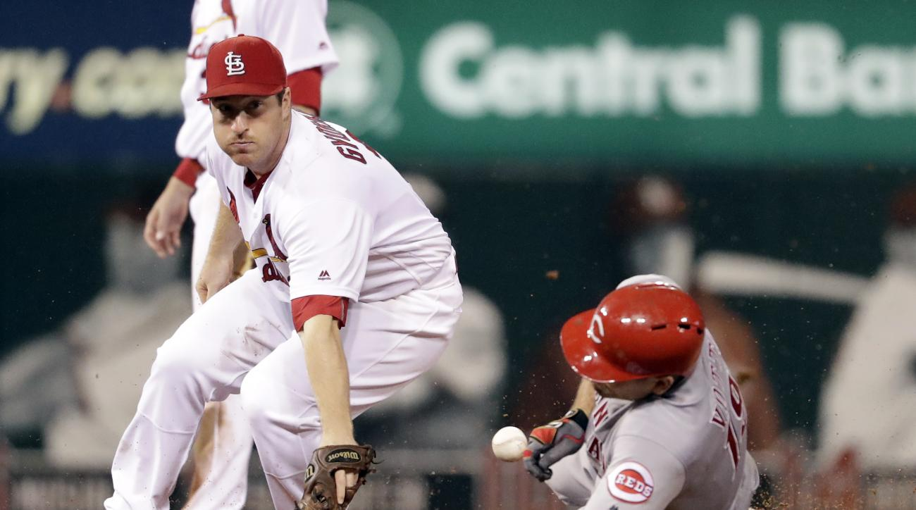 Cincinnati Reds' Joey Votto, right, is hit on the face with a ball while sliding into second for a double as the throw gets past St. Louis Cardinals second baseman Jedd Gyorko, left, during the eighth inning of a baseball game Thursday, Sept. 29, 2016, in