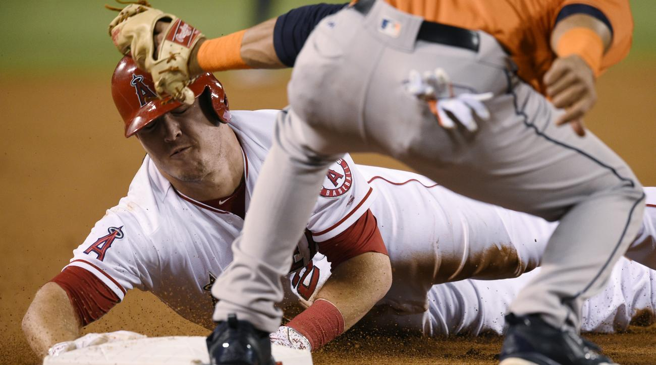 Los Angeles Angels' Mike Trout, back, steals third base ahead of the tag by Houston Astros third baseman Yulieski Gurriel, front, during the first inning of a baseball game in Anaheim, Calif., Friday, Sept. 30, 2016. (AP Photo/Kelvin Kuo)