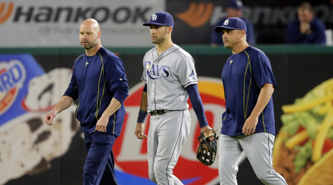 A member of the Tampa Bay Rays staff, left, manager Kevin Cash, right, and center fielder Kevin Kiermaier, center, walk in from the outfield after Kiermaier suffered an unknown injury in the sixth inning of a baseball game against the Texas Rangers on Sat
