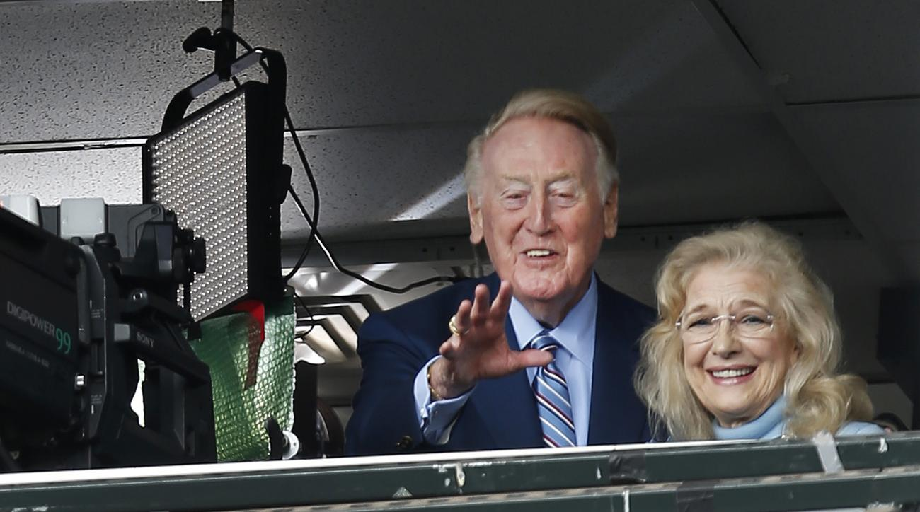 Los Angeles Dodgers announcer Vin Scully with his wife Sandi, waves to a fan before a baseball game between the San Francisco Giants and the Dodgers in San Francisco, Sunday, Oct. 2, 2016. (AP Photo/Tony Avelar)
