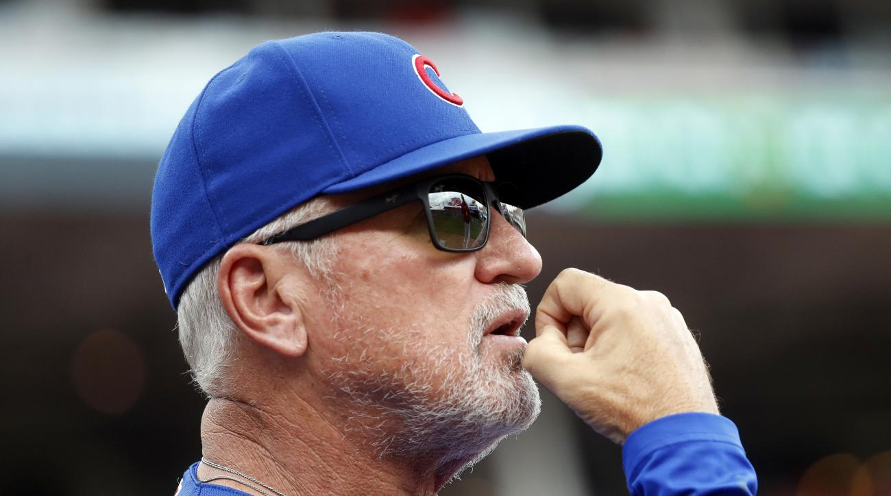 Chicago Cubs manager Joe Maddon warches from the dugout in the second inning of a baseball game against the Cincinnati Reds, Sunday, Oct. 2, 2016, in Cincinnati. (AP Photo/John Minchillo)