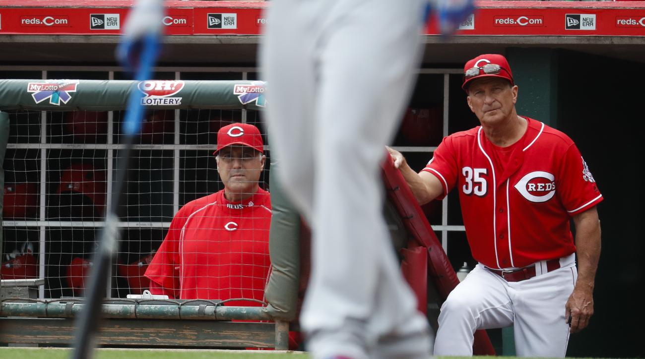 Cincinnati Reds manager Bryan Price, left, and bullpen coach Lester Strode (35) work the dugout in the first inning of a baseball game against the Chicago Cubs, Sunday, Oct. 2, 2016, in Cincinnati. (AP Photo/John Minchillo)