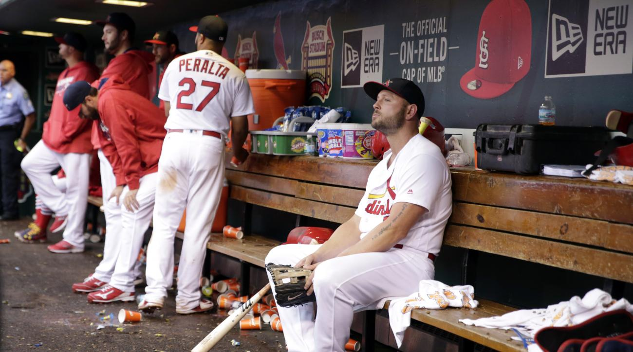 St. Louis Cardinals left fielder Matt Holliday, right, sits in the dugout after leaving a baseball game against the Pittsburgh Pirates during the ninth inning, Sunday, Oct. 2, 2016, in St. Louis. The Cardinals won 10-4 but were eliminated from playoff con