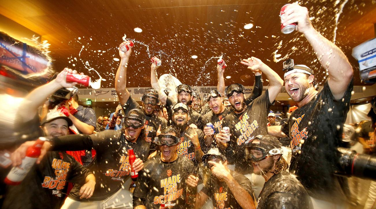 San Francisco Giants players celebrate in the clubhouse after clinching the second place wild card spot following their 7-1 win over the Los Angeles Dodgers in a baseball game in San Francisco, Sunday, Oct. 2, 2016. (AP Photo/Tony Avelar)