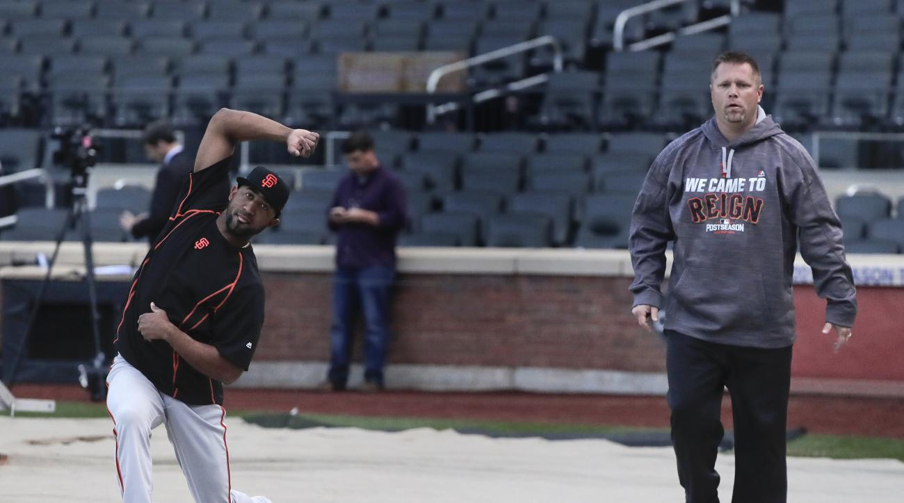 San Francisco Giants' Eduardo Nunez, left, stretches with a trainer during a team workout for the National League wildcard baseball game against the New York Mets, Tuesday, Oct. 4, 2016, in New York. (AP Photo/Julie Jacobson)
