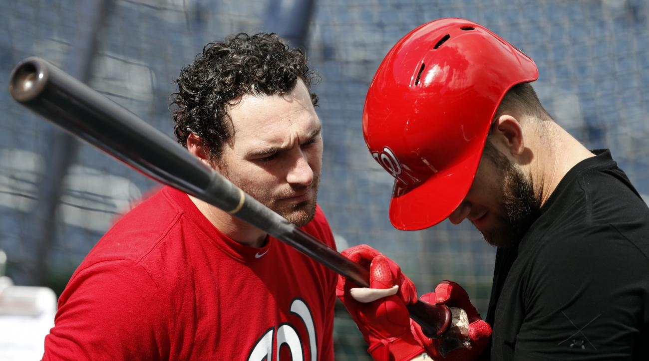 Washington Nationals second baseman Daniel Murphy, left, and right fielder Bryce Harper look at Harper's bat during baseball batting practice at Nationals Park, Wednesday, Oct. 5, 2016, in Washington. The Nationals host the Los Angeles Dodgers in Game 1 o