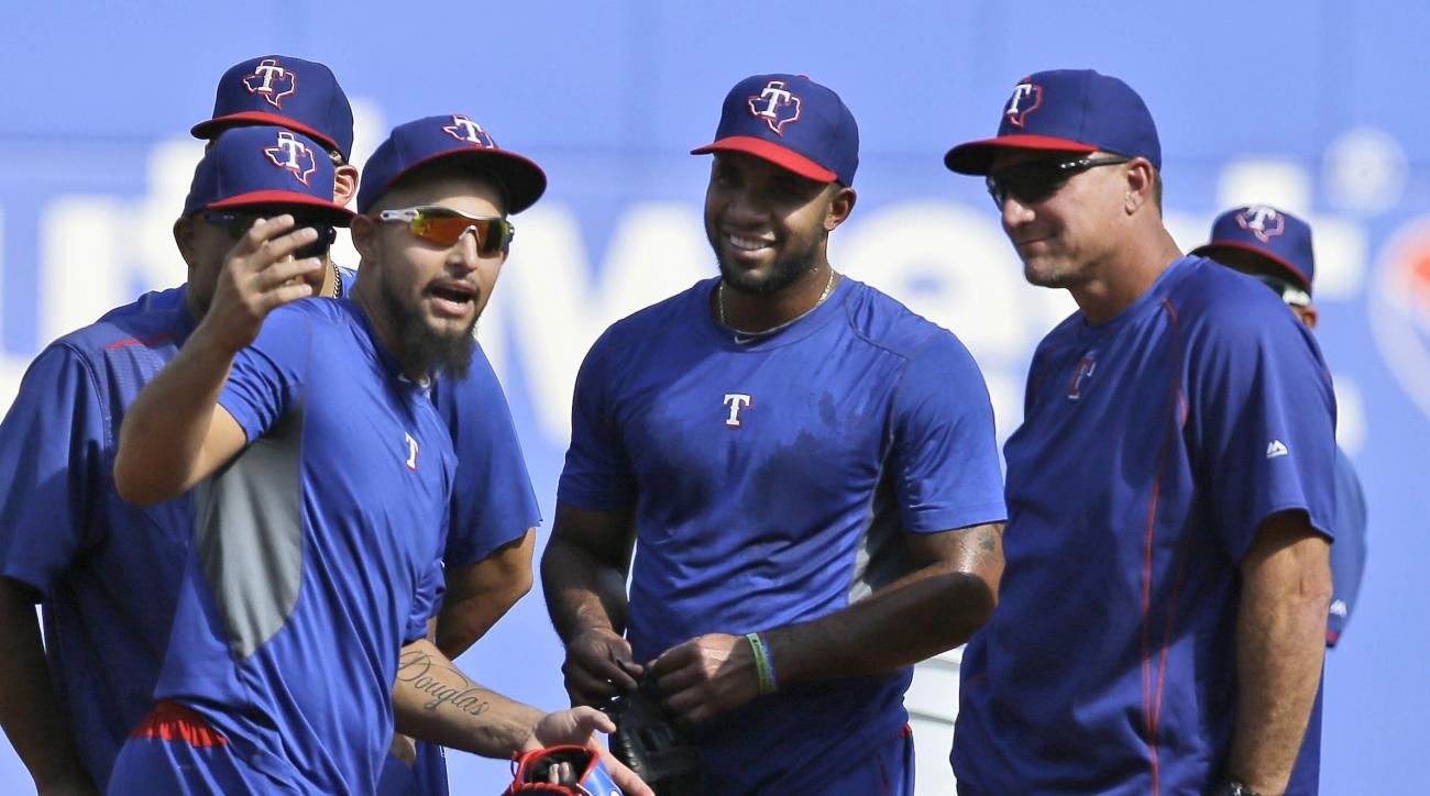 Texas Rangers second baseman Rougned Odor, left, talks with shortstop Elvis Andrus, center, and manager Jeff Banister during a baseball workout in Arlington, Texas, Wednesday, Oct. 5, 2016. The Rangers host the Toronto Blue Jays in Game 1 of the American
