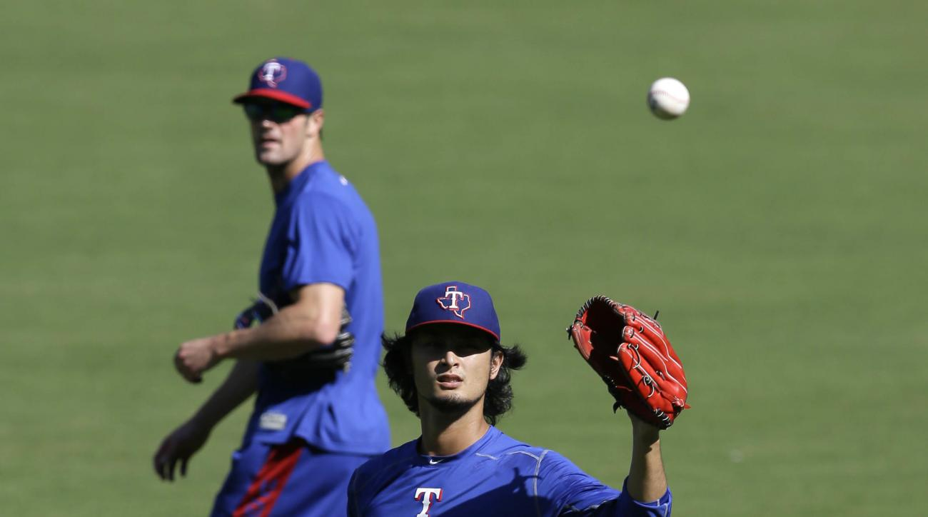 Texas Rangers pitcher Yu Darvish of Japan, front, warms up as teammate Cole Hamels looks on during a baseball workout in Arlington, Texas, Wednesday, Oct. 5, 2016. The Rangers host the Toronto Blue Jays in Game 1 of the American League Division Series on