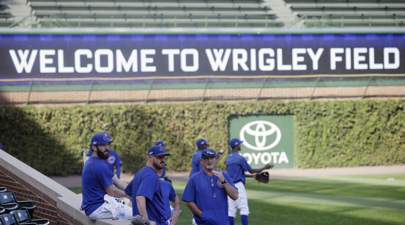 Chicago Cubs Chicago Cubs pitcher Jake Arrieta, left, relaxes as players warm up during baseball practice at Wrigley Field, Wednesday, Oct. 5, 2016, in Chicago. The Cubs host the winner of Wednesday's National League wild-card game between the New York Me