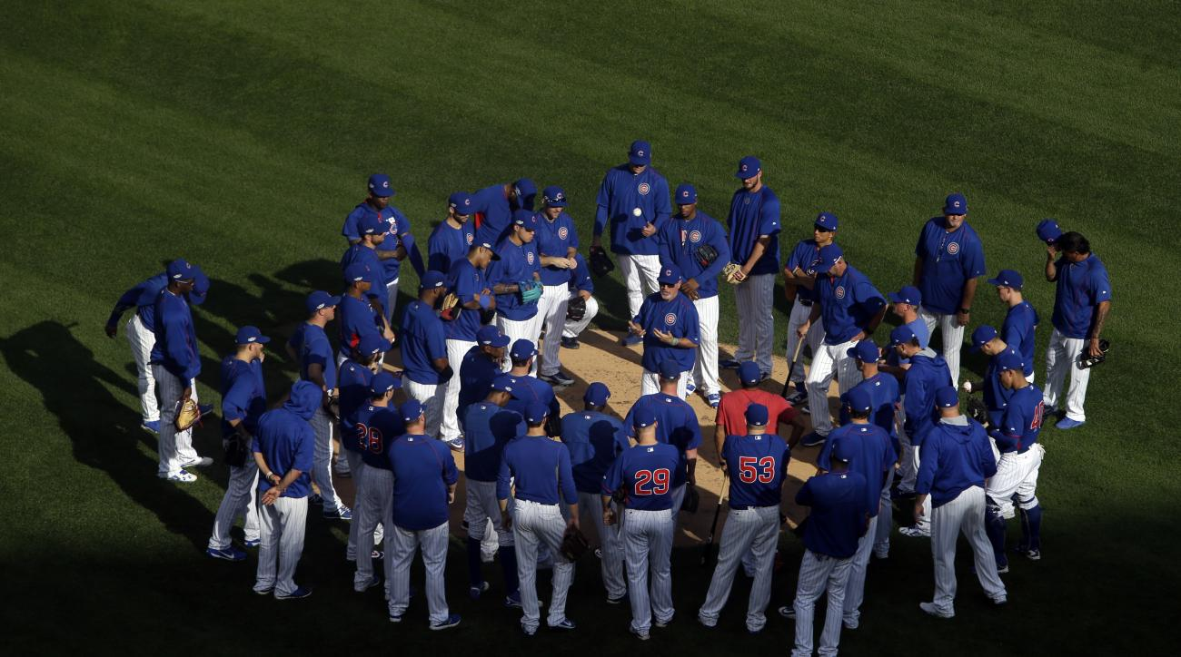 Chicago Cubs players gather around manager manager Joe Maddon, on the mound, during baseball practice at Wrigley Field, Wednesday, Oct. 5, 2016, in Chicago. The Cubs host the winner of Wednesday's National League wild-card game between the New York Mets a