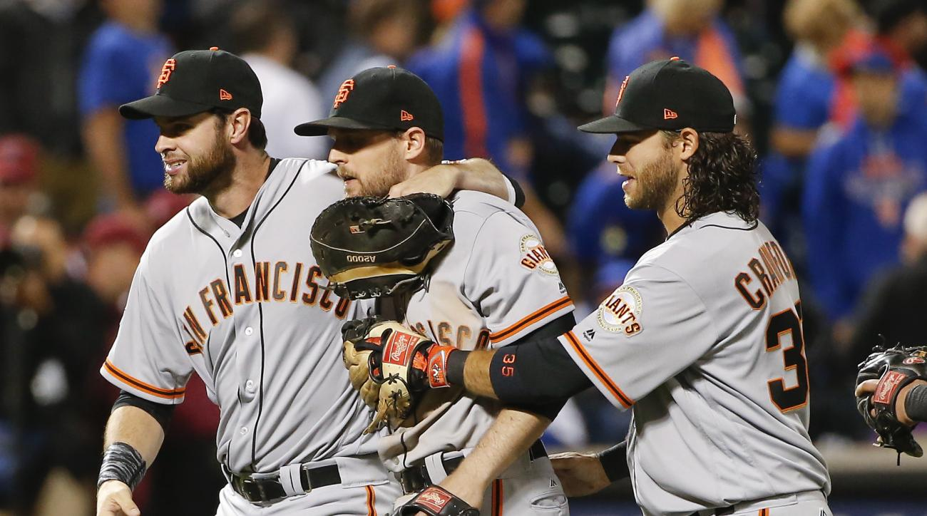 San Francisco Giants' Brandon Belt, left, and Brandon Crawford, right, celebrate with Conor Gillaspie after the Giants beat the New York Mets 3-0 in the National League wild-card baseball game, Wednesday, Oct. 5, 2016, in New York. (AP Photo/Kathy Willens