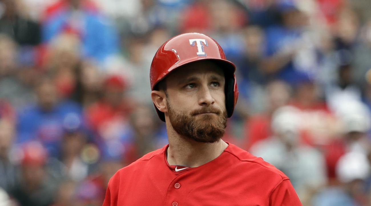 Texas Rangers' Jonathan Lucroy walks back to the dugout after striking out to end the bottom of the seventh inning stranding two runners on base in Game 2 of baseball's American League Division Series against the Toronto Blue Jays on Friday, Oct. 7, 2016,