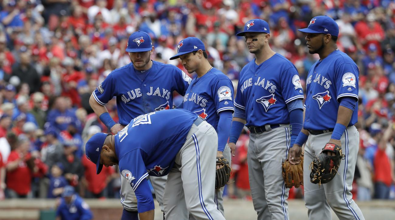 Toronto Blue Jays' Francisco Liriano leans over to grab the rosin bag as, from left rear, Josh Donaldson, Darwin Barney, Troy Tulowitzki and Edwin Encarnacion, right, stand by him after he was hit on the back of the head by a single off the bat of Texas R