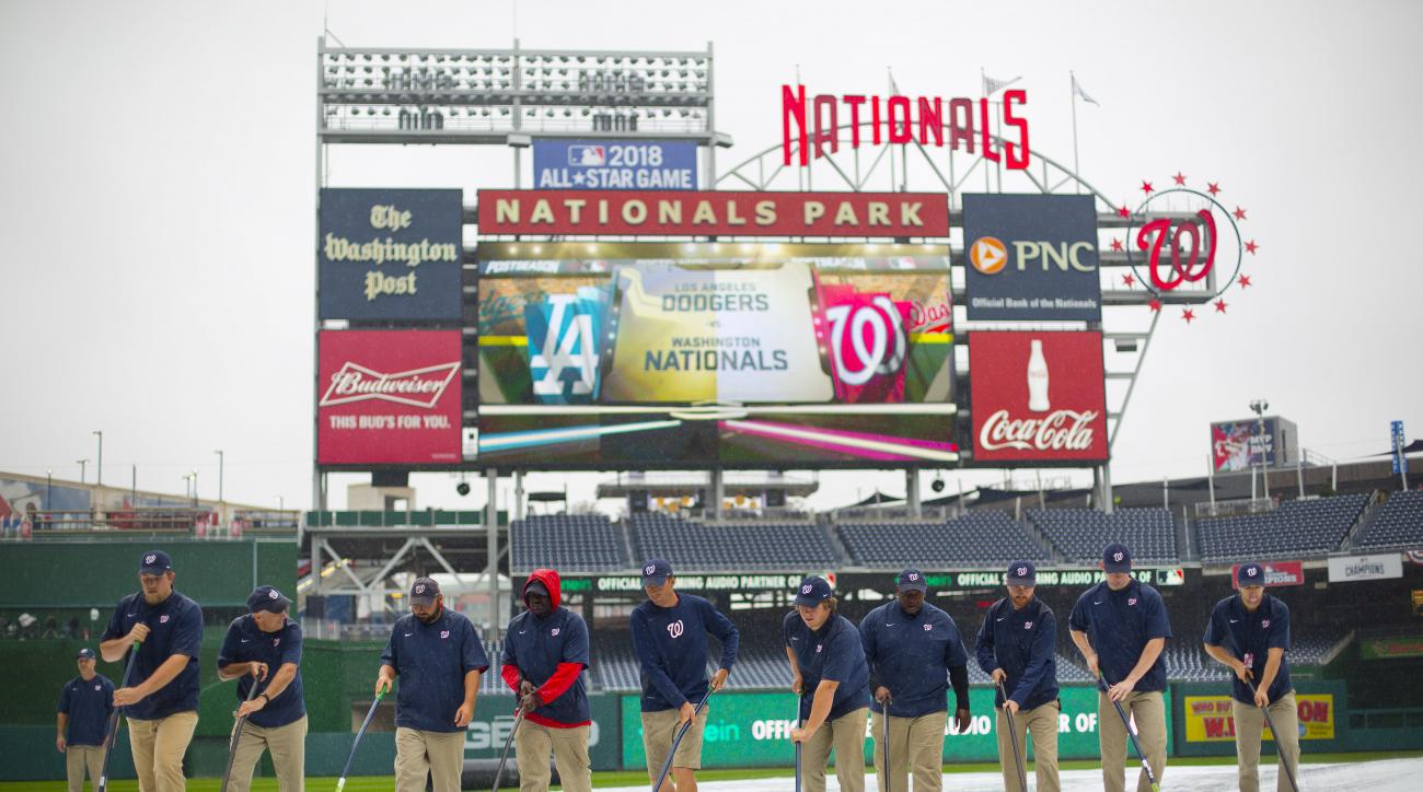 Members of the ground crew clear water off the infield tarp ahead of Game 2 of baseball's National League Division Series between the Los Angeles Dodgers and Washington Nationals at Nationals Park, Saturday, Oct. 8, 2016, in Washington. (AP Photo/Pablo Ma