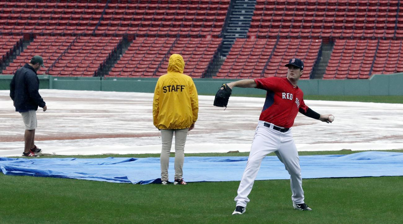 Boston Red Sox pitcher Drew Pomeranz tosses a baseball in the outfield in front of grounds crew workers at Fenway Park, Sunday, Oct. 9, 2016, in Boston. Rain postponed Sunday's scheduled Game 3 of baseball's American League Division Series between the Cle