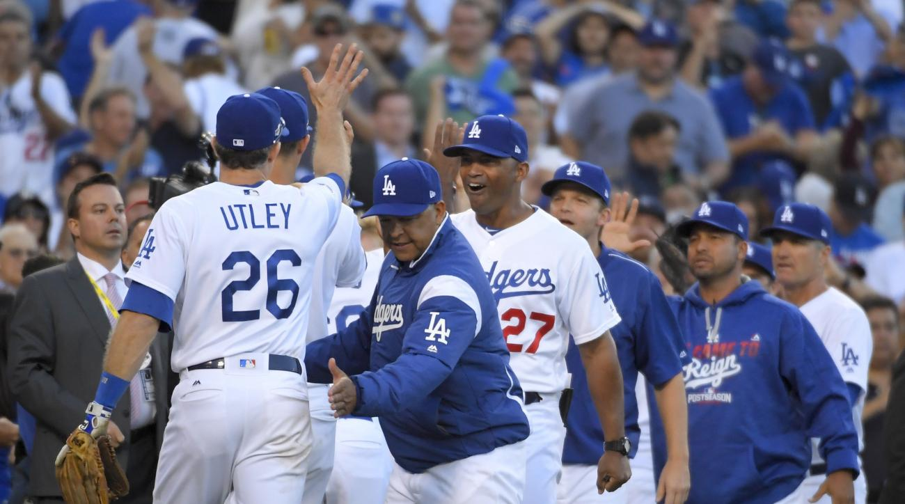 Los Angeles Dodgers manager Dave Roberts, second from left, celebrates with Chase Utley after the team's 6-5 win over the Washington Nationals during Game 4 of a baseball National League Division Series in Los Angeles, Tuesday, Oct. 11, 2016. (AP Photo/Ma
