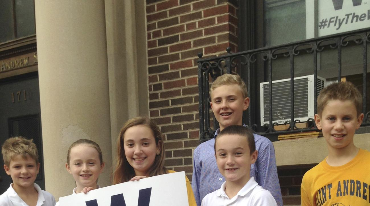 In this Oct. 6, 2016 photo, from left, Sean Leahy, Kaitlin Reap, Addison Casavechia, Connor Burns, blue shirt, Quinn Roberts and Max Oldham, students at Hawthorne Elementary School near Wrigley Field in Chicago, hold a Cubs W sign outside the school. It w