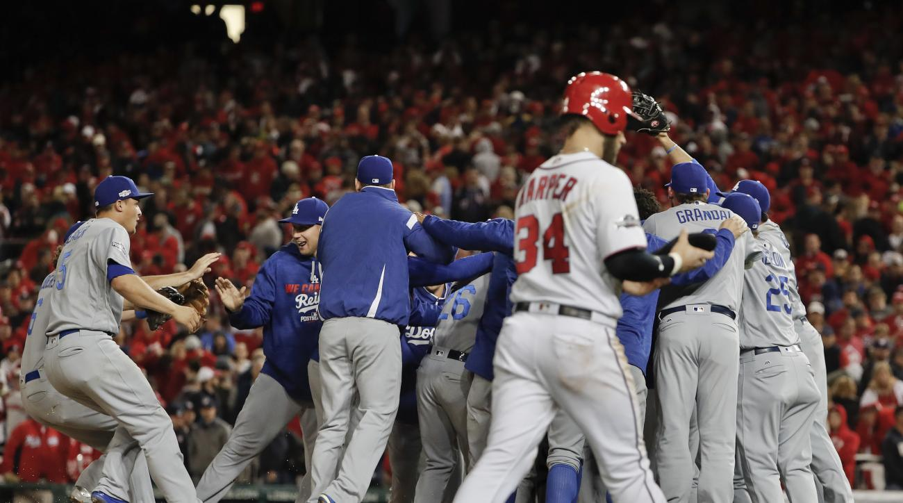 As Washington Nationals' Bryce Harper (34) walks from the field, the Los Angeles Dodgers celebrate a 4-3 win in Game 5 of a baseball National League Division Series, at Nationals Park early Friday, Oct. 14, 2016, in Washington. (AP Photo/Pablo Martinez Mo