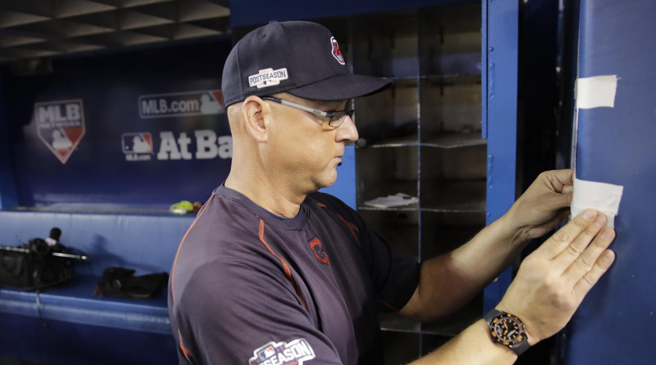 Cleveland Indians manager Terry Francona tapes up the line up before Game 4 of baseball's American League Championship Series in Toronto, Tuesday, Oct. 18, 2016. (AP Photo/Charlie Riedel)