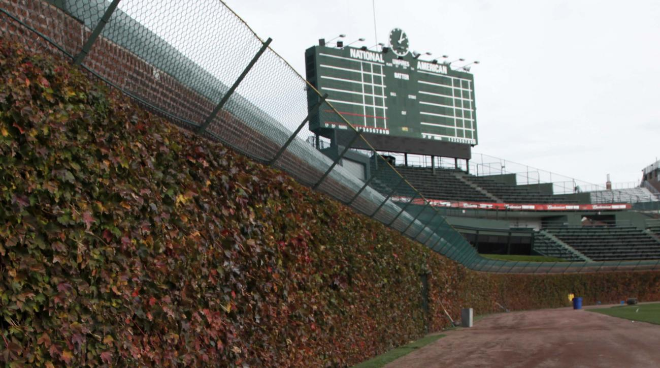 FILE - This Oct. 25, 2011, file photo, shows the outfield ivy and iconic manual scoreboard at Wrigley Field in Chicago. Wrigley Field has been the site of so much heartbreak that some fans who spend their whole lives waiting for a winner ask their familie
