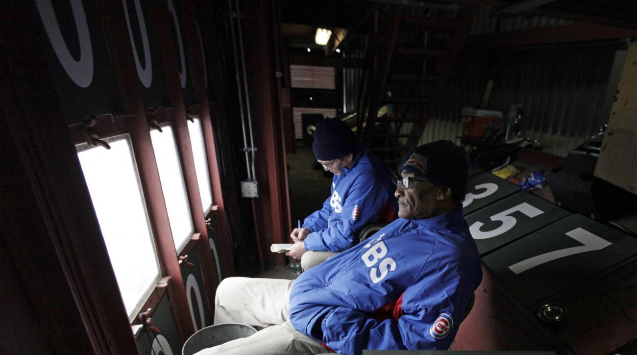 FILE - In this April 10, 2014 file photo, scoreboard operators Fred Washington, right, and Brian Helmus look out to the field from inside of the scoreboard at Wrigley Field during a baseball game between Pittsburgh Pirates and Chicago Cubs in Chicago. Fre