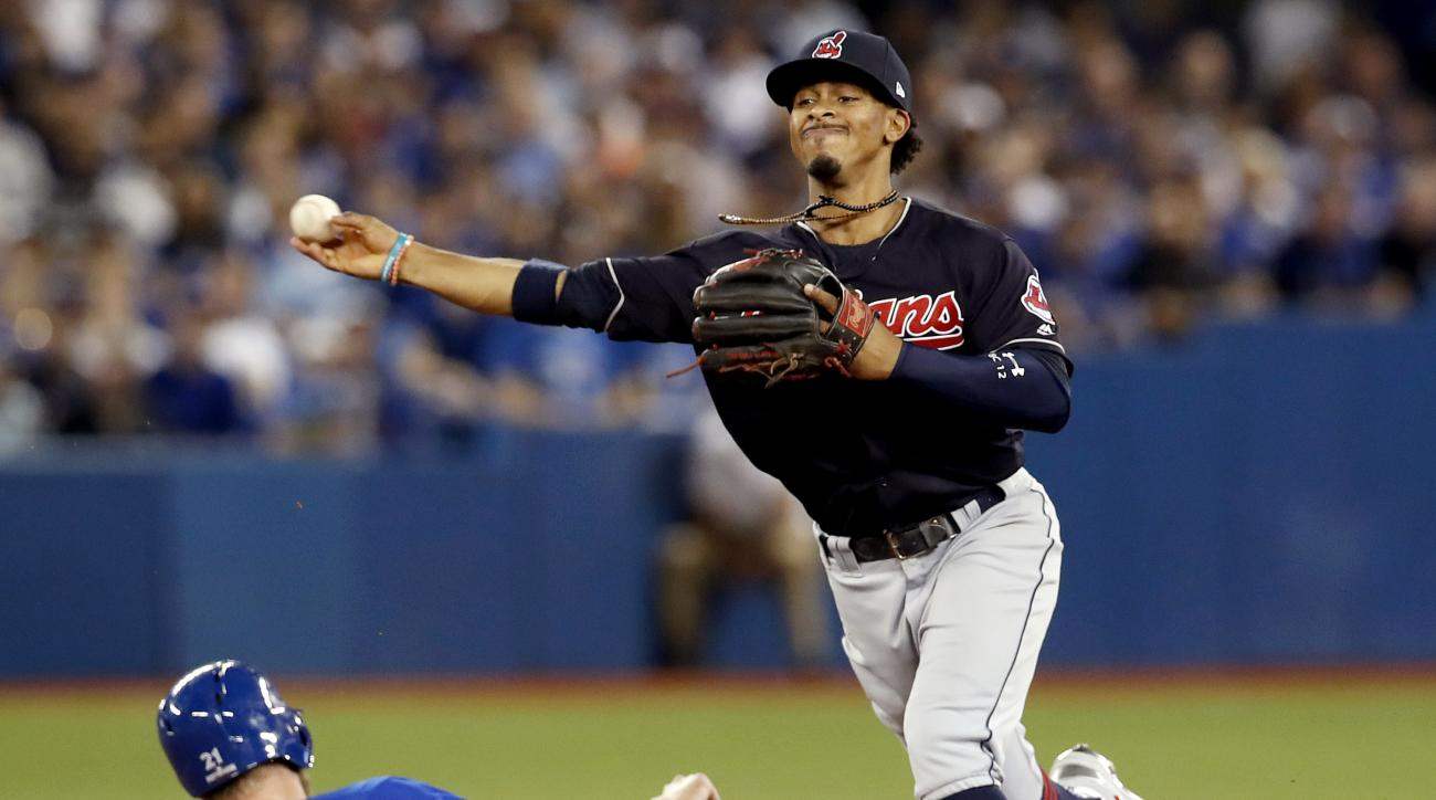 FILE- In this Tuesday Oct. 18, 2016, file photo, Cleveland Indians shortstop Francisco Lindor, right, forces Toronto Blue Jays' Michael Saunders out at second, but, fails to throws Ezequiel Carrera out at first during the second inning in Game 4 of baseba