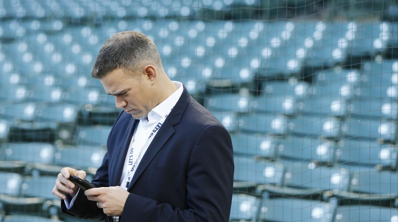 Chicago Cubs president for baseball operations Theo Epstein texts during batting practice before Game 6 of the National League baseball championship series against the Los Angeles Dodgers, Saturday, Oct. 22, 2016, in Chicago. (AP Photo/Charles Rex Arbogas