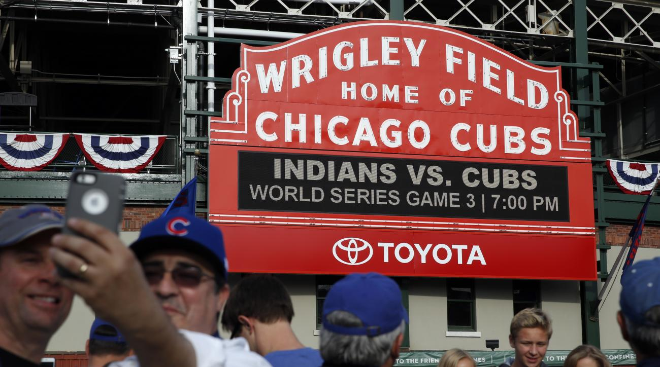 Fans take pictures in front of the Wrigley Field marquee before Game 3 of the Major League Baseball World Series between the Chicago Cubs and the Cleveland Indians, Friday, Oct. 28, 2016, in Chicago. (AP Photo/Nam Y. Huh)