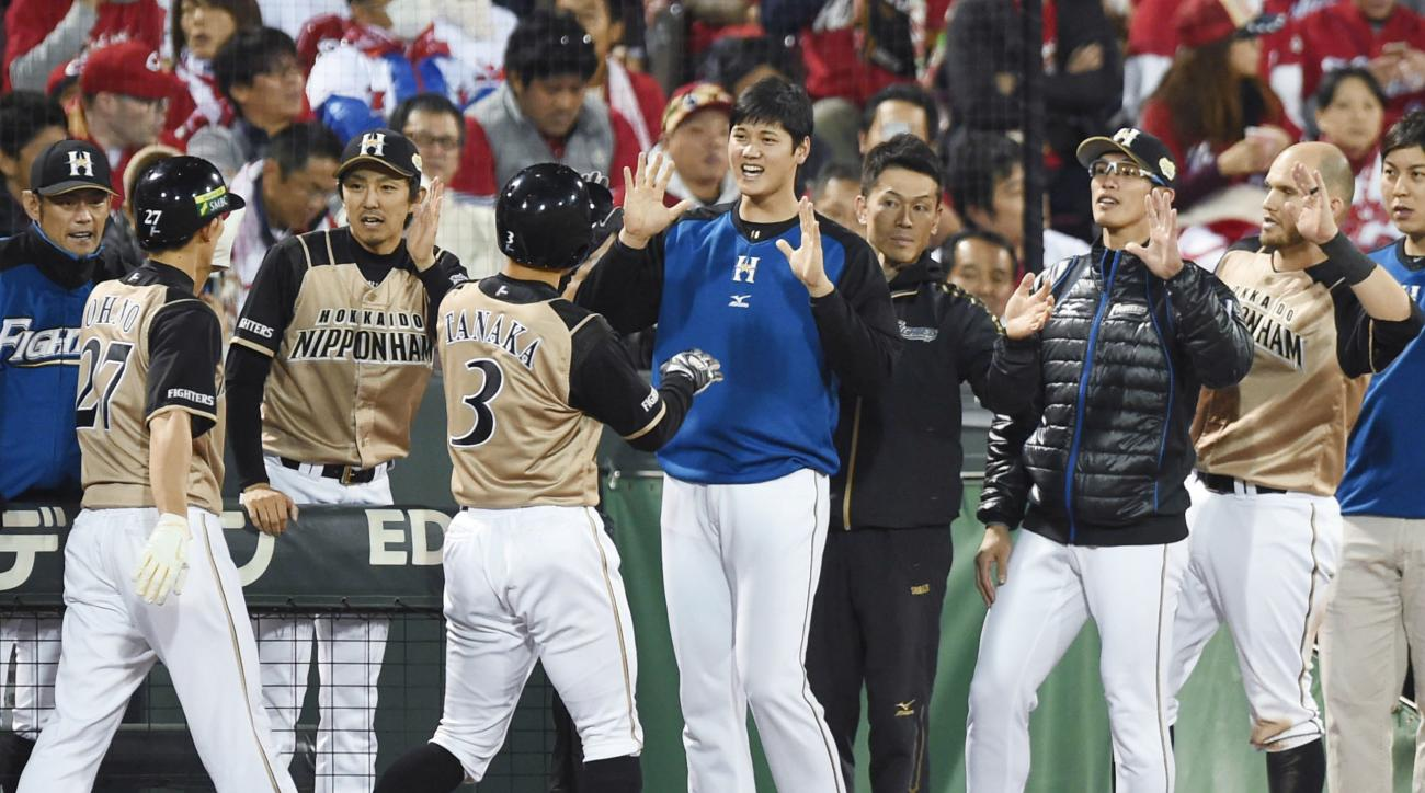 Nippon Ham Fighters' Kensuke Tanaka, (3), celebrates with teammates after scoring the go-ahead run on a triple hit by Haruki Nishikawa during the fourth inning of Game 6 of baseball's Japan Series against Hiroshima Carp at Mazda stadium in Hiroshima, Hiro