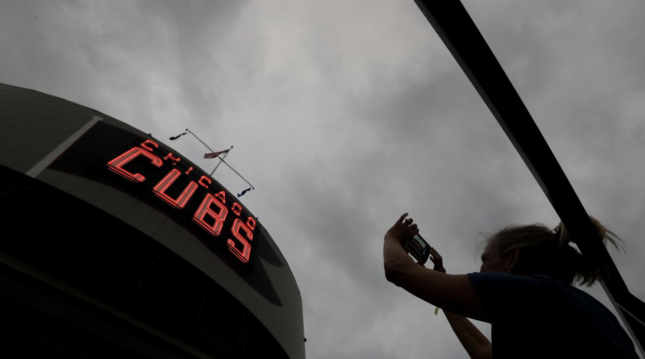 A fan takes a picture of Wrigley Field before Game 4 of the Major League Baseball World Series between the Cleveland Indians and the Chicago Cubs Saturday, Oct. 29, 2016, in Chicago. (AP Photo/Charlie Riedel)