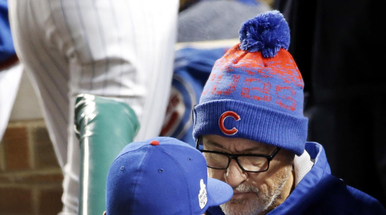 Chicago Cubs manager Joe Maddon, right, listens to Chris Coghlan in the dugout before Game 5 of the Major League Baseball World Series against the Cleveland Indians, Sunday, Oct. 30, 2016, in Chicago. (AP Photo/Nam Y. Huh)