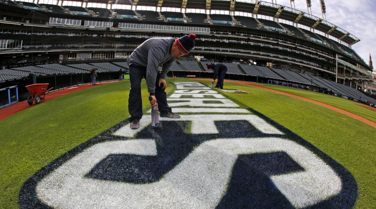 John Dileo, foreground, and Mathew Gudin of the Progressive Field ground crew touch up the World Series logo along the first baseline Monday, Oct. 31, 2016 in preparation for Tuesday night's Game 6 of the baseball World Series between the Cleveland Indian