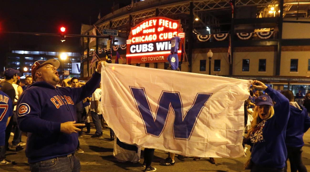 Chicago Cubs fans celebrate outside Wrigley Field in Chicago after the Cubs' 9-3 win over the Cleveland Indians in Game 6 of the baseball World Series in Cleveland, Tuesday, Nov. 1, 2016. The Cubs are scheduled to face the Indians in the decisive Game 7 W