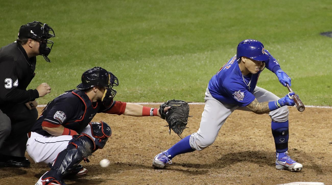 Chicago Cubs' Javier Baez strikes out on a bunt attempt during the ninth inning of Game 7 of the Major League Baseball World Series against the Cleveland Indians Wednesday, Nov. 2, 2016, in Cleveland. (AP Photo/Gene J. Puskar)