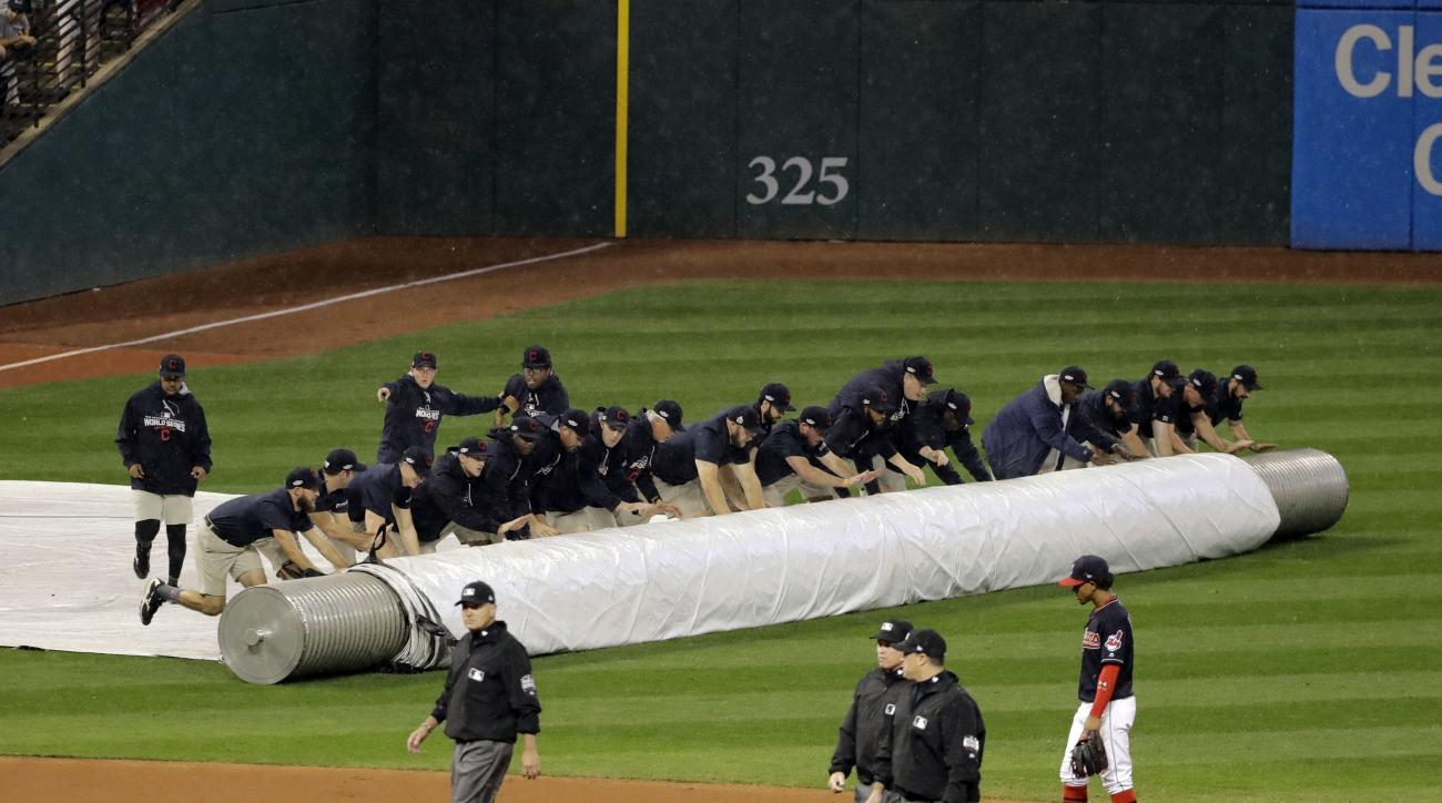 Workers cover the infield at Progressive Field during the 10th inning of Game 7 of the Major League Baseball World Series between the Cleveland Indians and the Chicago Cubs Wednesday, Nov. 2, 2016, in Cleveland. (AP Photo/Gene J. Puskar)