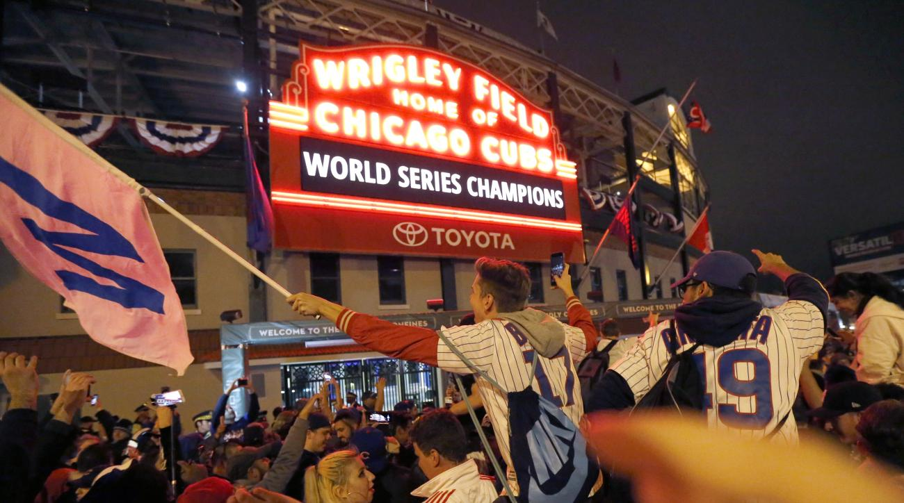 Chicago Cubs fans celebrate in front of Wrigley Field in Chicago on Wednesday, Nov. 2, 2016, after the Cubs defeated the Cleveland Indians 8-7 in Game 7 of the baseball World Series in Cleveland. (AP Photo/Charles Rex Arbogast)