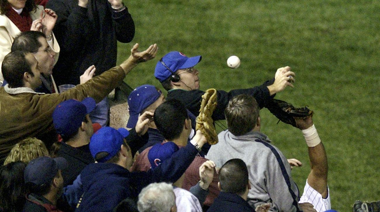 FILE - In this Oct 14, 2003, file photo, Steve Bartman catches a ball as Chicago Cubs left fielder Moises Alou's arm is seen reaching into the stands, at right, against the Florida Marlins in the eighth inning during Game 6 of the National League champion