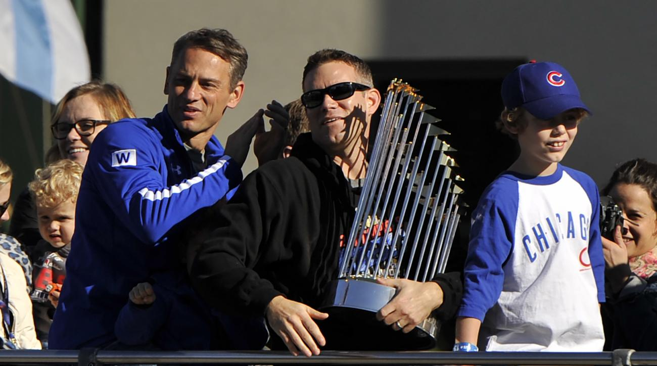 Chicago Cubs president of baseball operations Theo Epstein holds the Commissioner's Trophy while son, Jack, right, and Chicago Cubs vice president of baseball operations and general manager Jed Hoyer, left, look on outside Wrigley Field during a parade ho