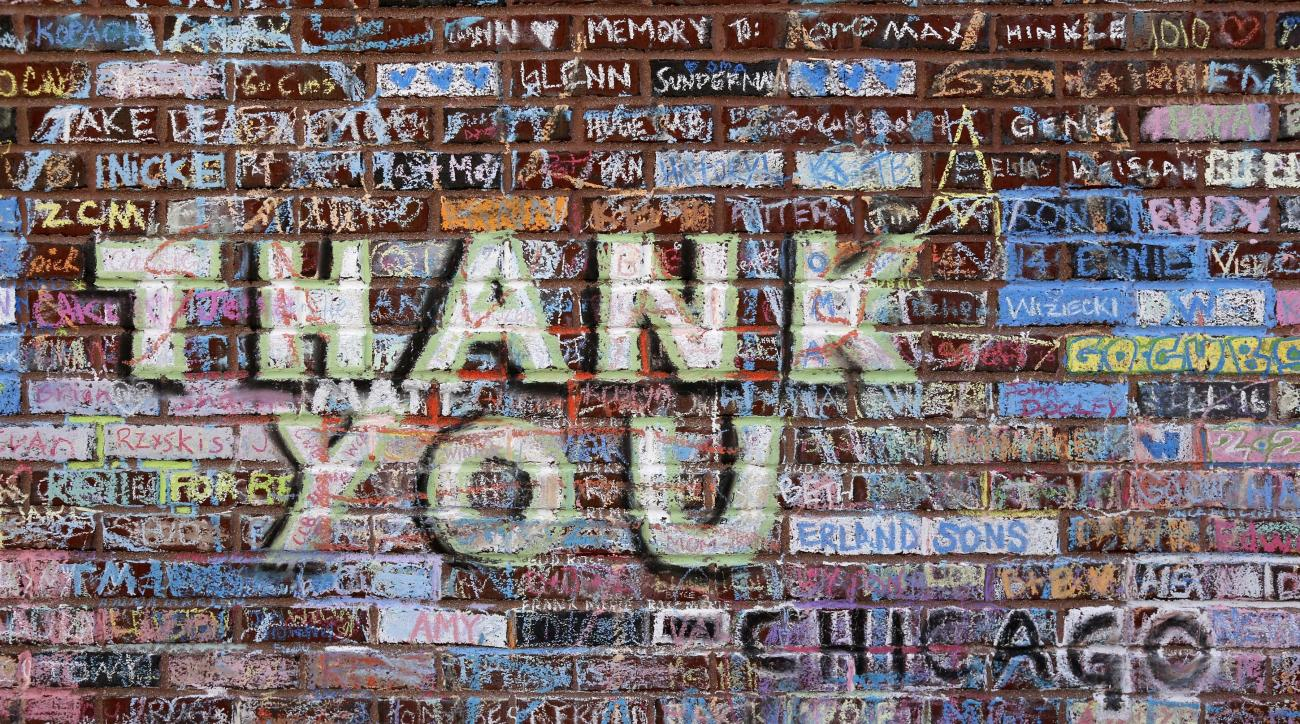 Messages in support of the Cubs' championship run and in remembrance of friends and family who never saw the Cubs win the World Series, are written and drawn in chalk on an outer wall at Wrigley Field Monday, Nov. 7, 2016, in Chicago. Fans started writing