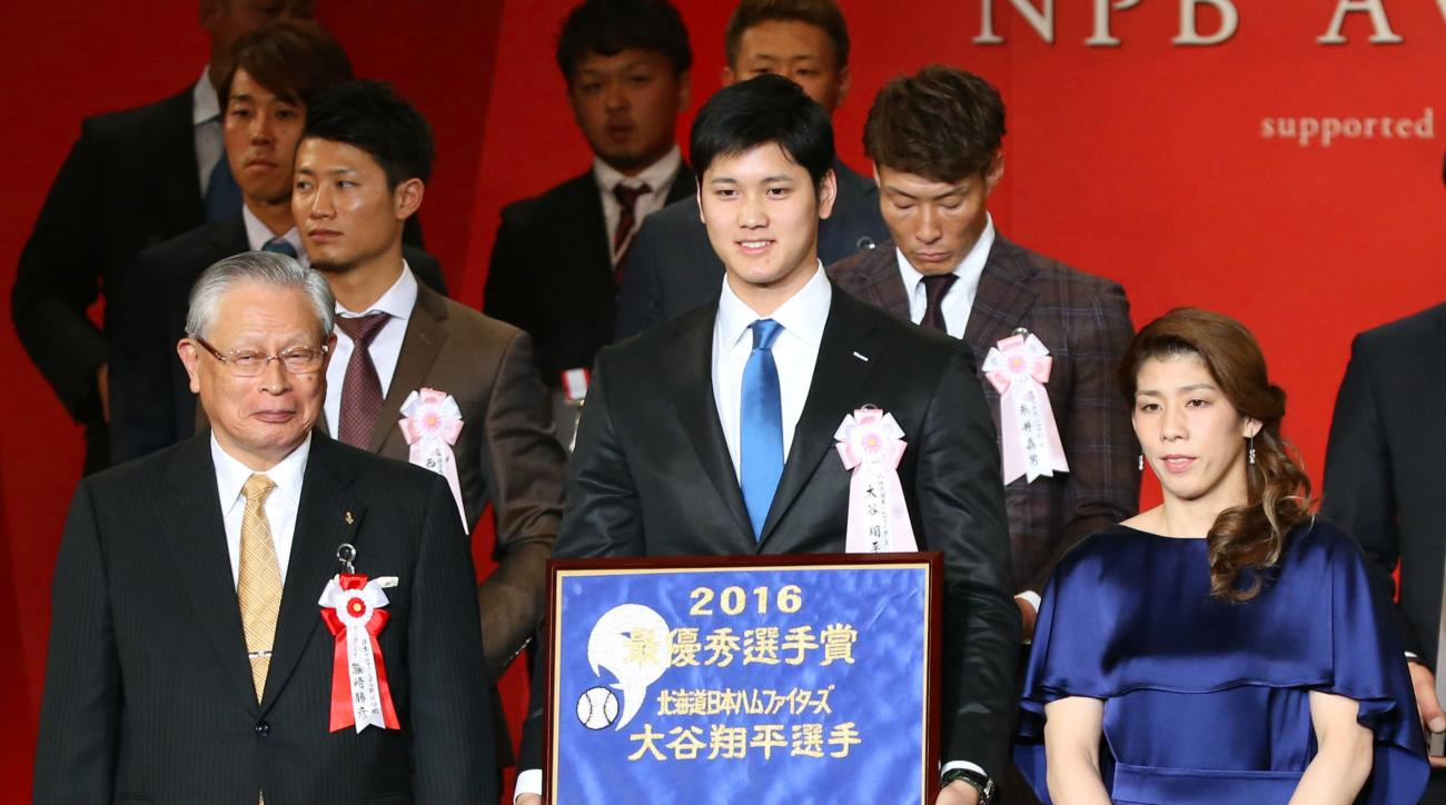 Shohei Otani, center, of the Hokkaido Nippon Ham Fighters, accompanied by Nippon Professional Baseball Commissioner Katsuhiko Kumazaki, left, and Japan's freestyle wrestling Olympic medalist Saori Yoshida, smiles after being named Most Valuable Player of