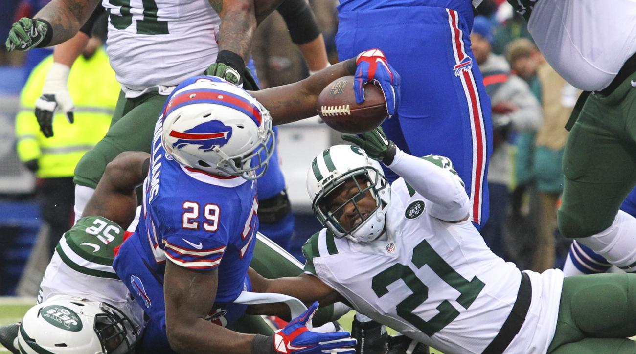 Buffalo Bills running back Karlos Williams (29) reaches the ball over the goal line for a touchdown in front of New York Jets' Marcus Gilchrist (21) during the first half of an NFL football game Sunday, Jan. 3, 2016, in Orchard Park, N.Y. (AP Photo/Bill W